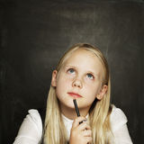 Little girl on blackboard background Stock Images