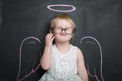 Little girl at the blackboard with wings and halo Royalty Free Stock Photography