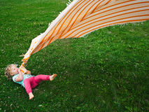 Little girl with a blanket. A cute little girl lying in the grass, playing with an orange blanket with white stripes stock photos