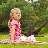 Little girl on a blanket looks into the distance Stock Photography