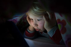 Little Girl in Blanket Staring at Glowing Tablet Screen Stock Photography