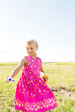 Little girl with blond curly hair and pink dress is played with soap bubbles in the field. Little girl with blond curly hair and pink dress is played with soap Stock Images