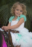 Little Girl on a Pony. A little girl with blond hair and blue eyes,  and wearing a turquoise and white princess dress with a white ruffle, is having fun riding Stock Images