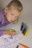 Little girl with blond hair draws Stock Photo