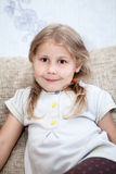 Little girl with blond hair sitting on the couch. Little Caucasian girl with blond hair sitting on the couch Royalty Free Stock Photos