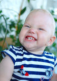 Little girl with blond hair smiling and grimacing. On green plant background Stock Images