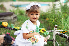 Little girl with blond hair in a white dress with embroidery. Little girl with blond hair and white dress sitting in the park and played with animal figurines Royalty Free Stock Photos