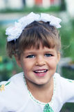 Little girl with blond hair in a white dress with embroidery. Little girl with blond hair and white dress sitting in the park and smiling Stock Images
