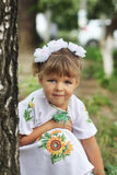 Little girl with blond hair in a white dress with embroidery. Little girl with blond hair and in a smart white dress hiding behind a tree in the park Stock Photos