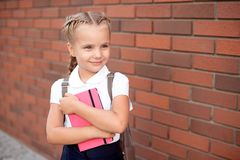 Little girl with blond hair in a white shirt and blue skirt holds an empty board near the upper wall. royalty free stock images
