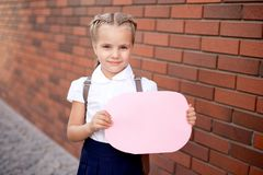 Little girl with blond hair in a white shirt and blue skirt holds an empty board near the upper wall royalty free stock photos