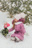 Little girl with blond long hair sitting in the snow holding a frozen flower in winter time Royalty Free Stock Photo