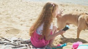 Girl eats ice cream and feeds the dog outdoors. The little girl with blond wavy hair in pink clothes eats ice cream and feeds the dog on the beach on the river stock video