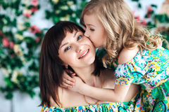 Little girl blonde in a bright dress kisses mom on the cheek, Close-up Royalty Free Stock Photos