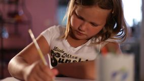 Little girl blonde draws a pencil.сlose-up.blurred background. stock footage