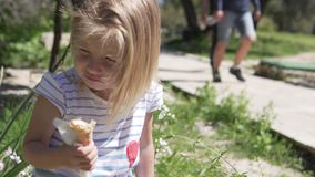 Little girl blonde eats ice cream in a waffle cup on a hot day. In the park stock footage