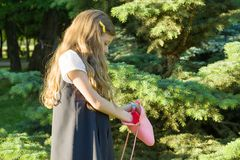 Little girl blonde with long curly hair with a pink rubber handbag in the park. The girl opened and looks in handbag royalty free stock photography