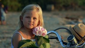 The little girl the blonde sits with a pink flower in hands on the white moped on sand by the sea. The beautiful girl. On this video you can see as the close stock footage