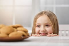 Little girl is looking on delicious cookies. stock photography