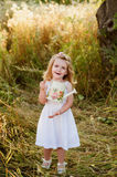 Little girl blonde in a white dress in garden with watering, laughing, childhood, relaxation, serenity Royalty Free Stock Photos