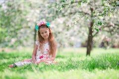 Little girl in blooming cherry tree garden outdoors Stock Photos