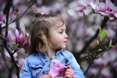 Little girl in blossoming garden on spring day. Child with magnolia flowers, beauty. Spring, nature, romance. Kid beauty, look, hair. New life youth growth royalty free stock photos