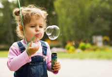 Little girl blow bubbles Stock Photography