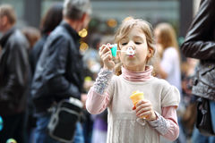 A little girl blow bubbles on the street Stock Photography