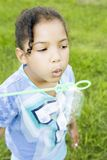 Little girl blowing bubbles. Little girl holding wand blowing bubbles royalty free stock photos