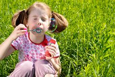 Little girl blowing bubbles Stock Photography
