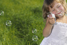 Little Girl Blowing Bubbles. On green grass Royalty Free Stock Photography