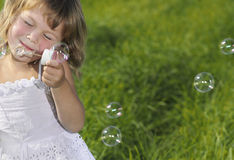 Little Girl Blowing Bubbles. On green grass stock images