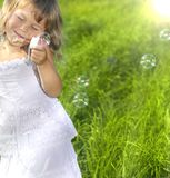 Little Girl Blowing Bubbles. On green grass stock image