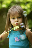 Little girl blowing bubbles outside. A little girl blows bubbles outside in the summertime Royalty Free Stock Images