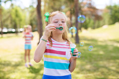 Little Girl Blowing Bubbles. Shot of blond and freckled little girl with ponytails wearing striped t-shirt blowing bubbles in green park on sunny day. Similar royalty free stock photos