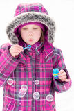 Little girl blowing bubbles in snow. Little girl playing outdoors in snow, blowing bubbles royalty free stock image