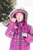 Little girl blowing bubbles in snow. Little girl playing outdoors in snow, blowing bubbles stock photo