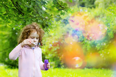 A little girl blowing bubbles. Stock Photo