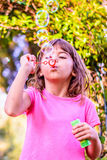 Little girl blowing bubbles. Little girl is blowing bubbles with the wand in the park Royalty Free Stock Images