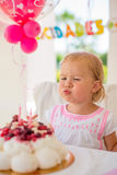 Little Girl Blowing Candles on Her Birthday Cake. Cute Little Girl Blowing Candles on Her Birthday Cake  Outdoor Party on Bright Terrace with Pink Decoration Royalty Free Stock Images