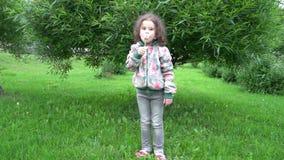Little girl blowing on a dandelion. Little girl blowing on the dandelion on background green wood stock footage