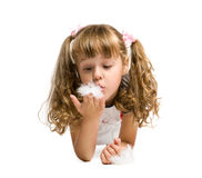 Little girl blowing on a feather Stock Photo