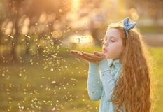 Little girl blowing gold confetti with her hand. stock image
