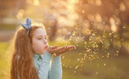 Little girl blowing gold confetti with her hand royalty free stock photography