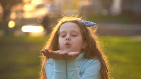 Little girl blowing gold confetti with her hand. Holiday, happy childhood, healthy lifestyle concept stock footage