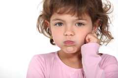Little girl blowing her cheeks. As she is unimpressed Royalty Free Stock Photography