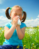Little girl is blowing her nose. While sitting on green meadow Royalty Free Stock Photo