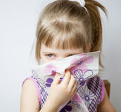 Little girl blowing her nose Royalty Free Stock Photo