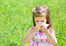 Little girl is blowing her nose. On green meadow Stock Photo