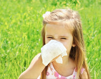 Little girl is blowing her nose on green meadow Stock Photo